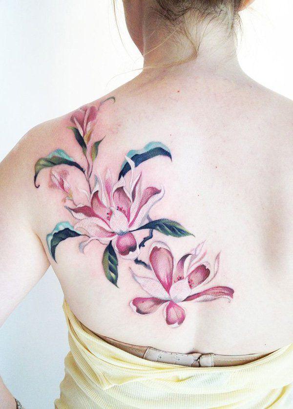Pink magnolia flower tattoo on the back - a feminine tattoo idea for women