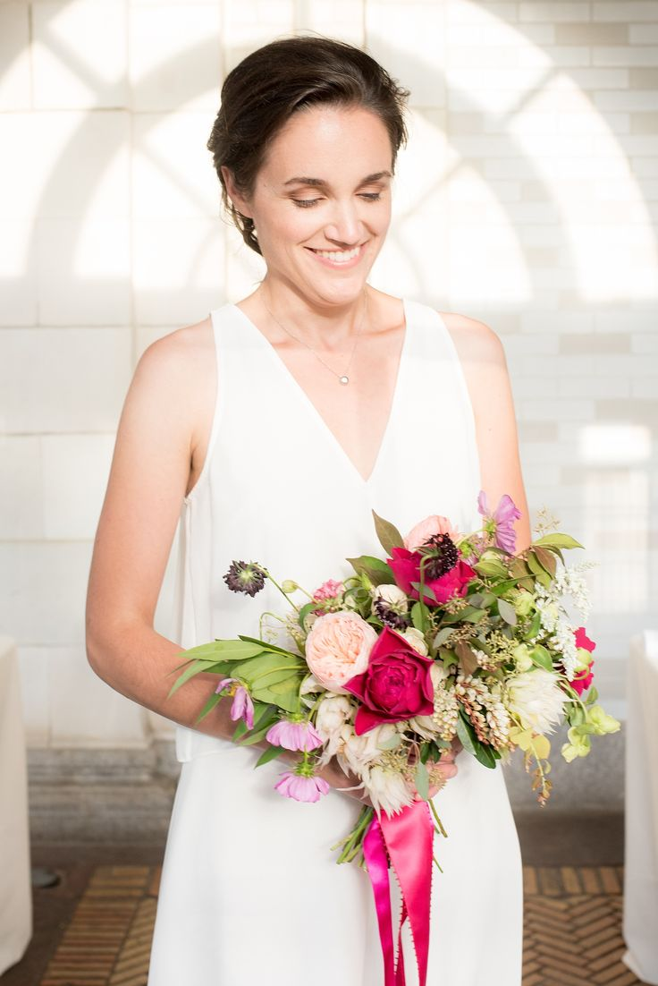 Mikkel Paige Photography photo of an all-white dressed bridesmaid holding a pink...
