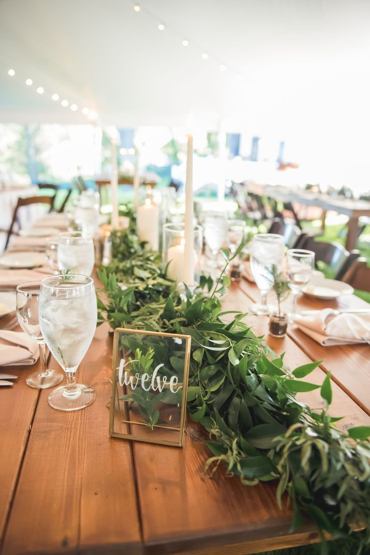 Green garland centerpiece with glass table numbers