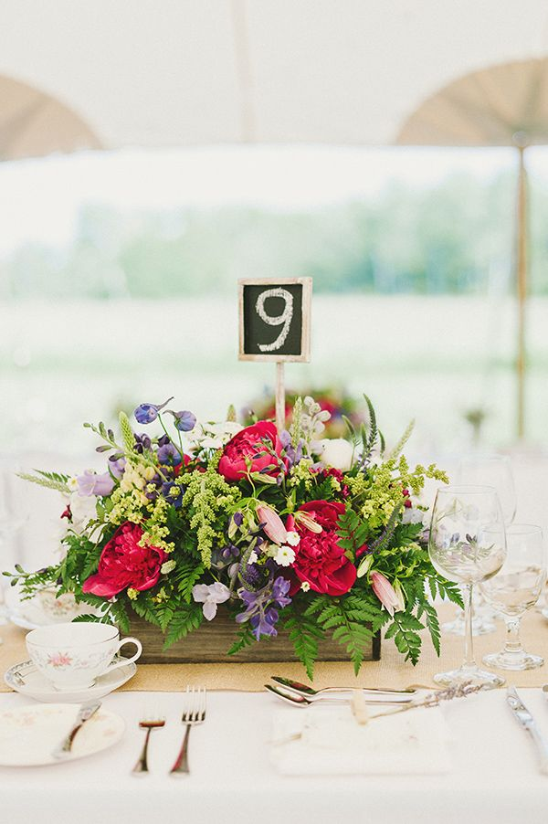 love the pops of bright pink in this wildflower centerpiece #tablenumber #wildfl...