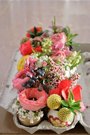 Little flower arrangements in egg shells in an egg carton.